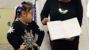 A girl with her hands on her hips looking over to her notebook the teacher is holding and pointing to the top of the page.