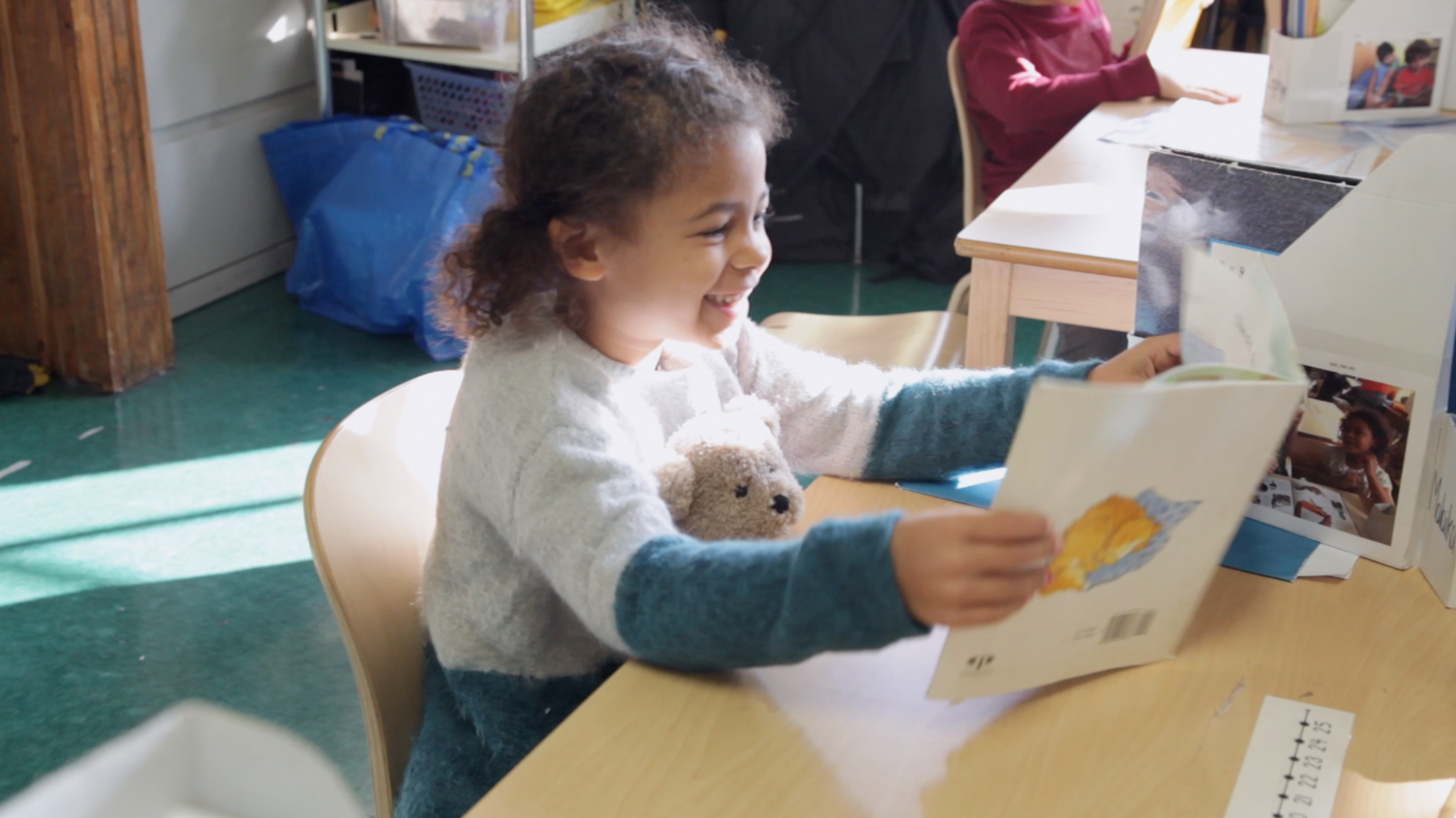 Student reading and smiling with her teddy bear in her lap